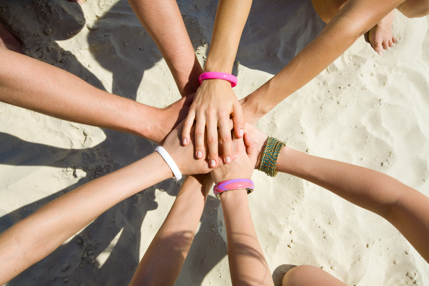 hands of young people stretching to the center on beach